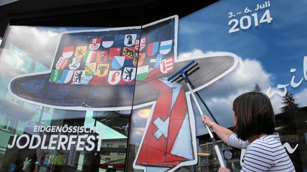 Eine Frau putzt die Fensterscheibe, auf der das Jodlerfest-Logo prangt.