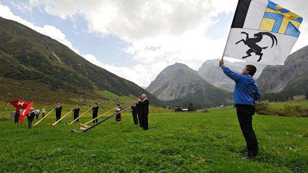 Fahnenschwinger und Alphornbläser inmitten einer Alpwiese.