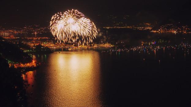 Ein Feuerwerk, das sich nachts in der glatten Oberfläche eines Sees spiegelt.