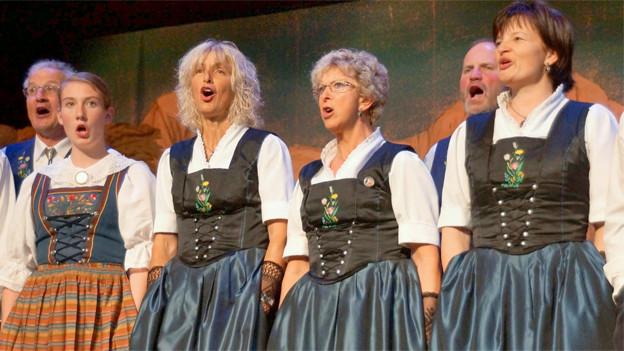 Vier Jodlerinnen und zwei Jodler in ihren Trachten während eines Auftritts.