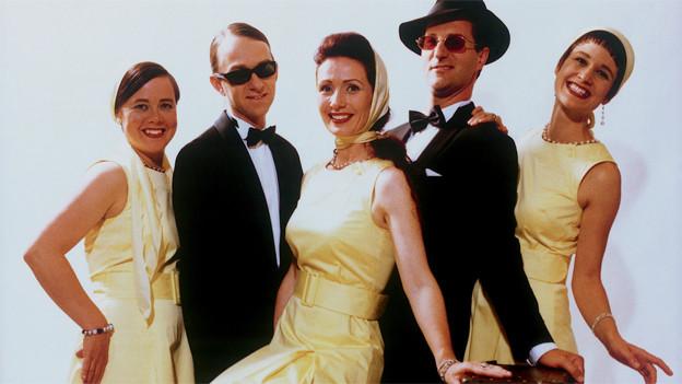 Die drei Sängerinnen tragen auf dem Gruppenbild gelbe Röcke, die zwei Sänger schwarze Anzüge.