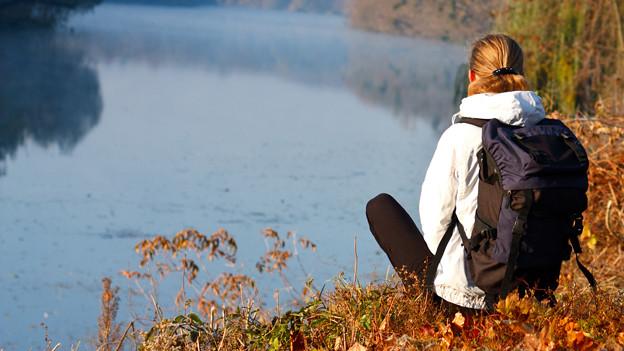 Eine Frau mit Rucksatz sitzt auf einer Anhöhe und blickt auf den darunterliegenden See.