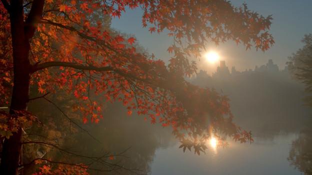 Die Sonne spiegelt sich beim Untergang in einem kleinen See.