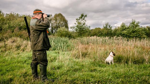Ein Jäger ist mit seinem Hund unterwegs und sucht die Umgebung mit einem Fernglas nach einer möglichen Beute ab.