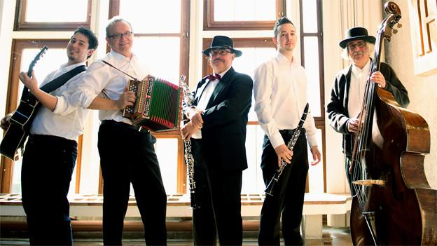 Die fünf Musiker posieren mit ihren Instrumenten in einem hellen Raum fürs Gruppenfoto.