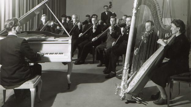 Schwarz-Weiss Fotografie einem Orchester bei der Probe. Ein Mann am Flügel, mehrere Männer mit Geige und eine Frau an der Harfe.