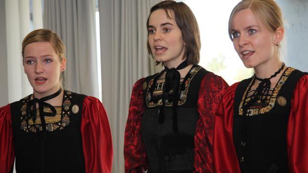 Drei junge Damen mit scharlachroten Trachtengewändern.