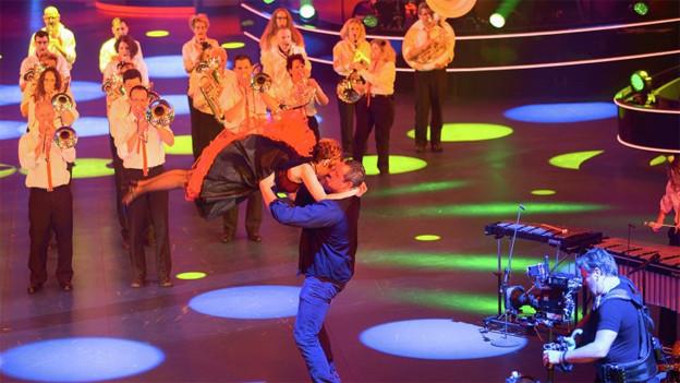 Die Musikanten stehen beim Spiel in einer Formation während der Schwingerkönig eine Tänzerin in die Höhe wirft.