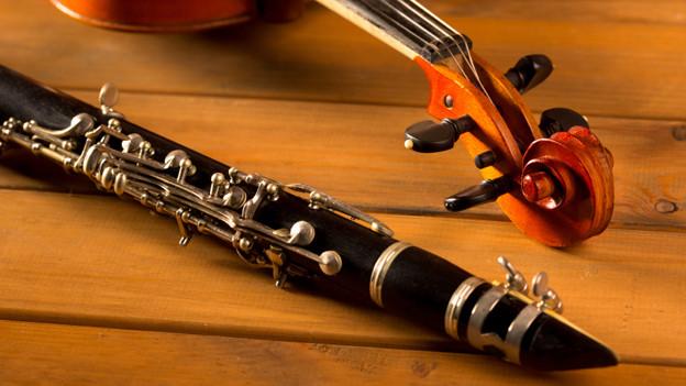 Eine schwarze Klarinette liegt vor dem Hals einer Violine.