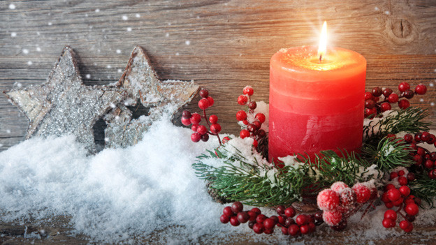 Vor einer Holzwand stehen zwei hölzerne Sterne und eine brennende rote Kerze.