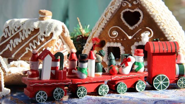 Auf einem Zug aus Holz sitzen hölzerne Schneemänner und fahren an einem Lebkuchenhaus vorbei.