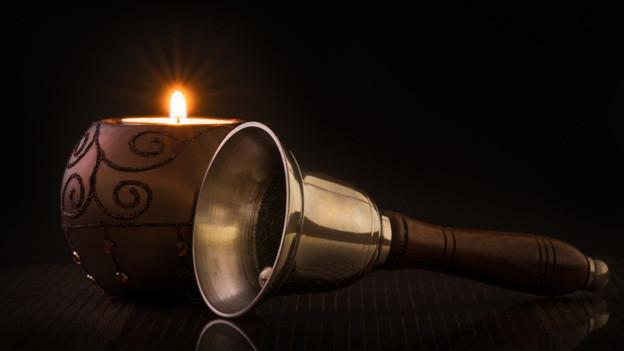 Eine Handglocke liegt neben einer braunen Kerze.