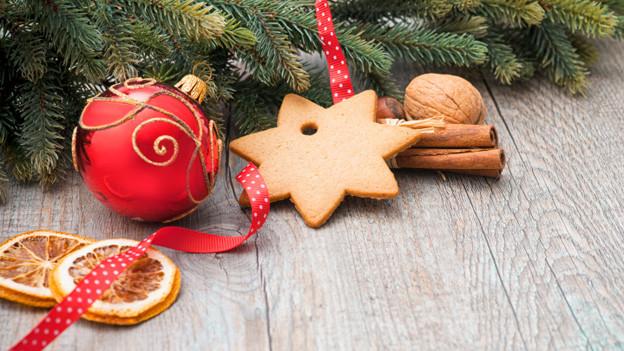 Eine rote Weihnachtskugel, zwei getrocknete Orangenscheiben, ein sternförmiges Weihnachtsguetzli, ein paar Zimtstangen und eine Baumnuss liegen vor ein paar Tannenzweigen.