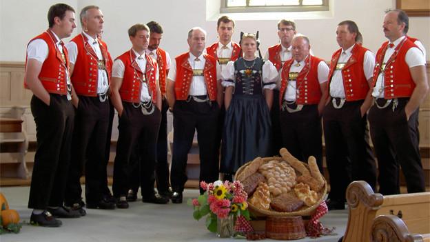 Eine Gruppe von Sängern und eine Sängerin in Appenzellertracht während eines Jodelvortrags in der Kirche.
