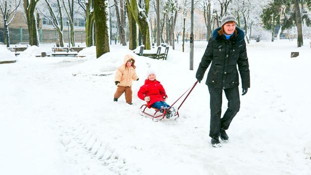 Mutter mit Kindern auf Schlitten