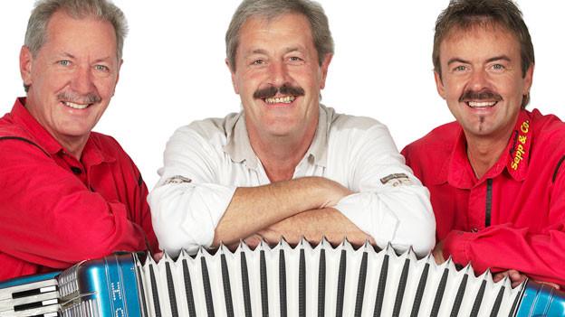 Drei Männer mit Schnauz posieren nebeneinander und stützen die Arm auf einem ausgezogenen Akkordeon auf.