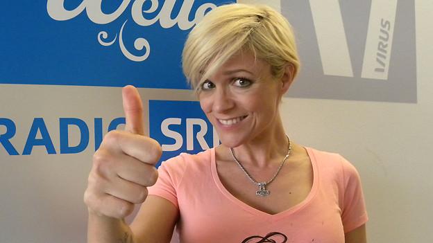 Michelle hält dem Daumen hoch, vor dem Logo von SRF Musikwelle.