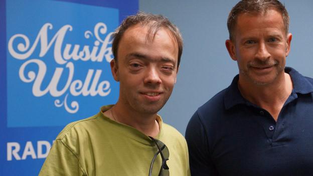 HIt-Welle MOderator mit Martin Brugger im lindgrünen T-Shirt zu Gast im Studio. Martin hat sich eine Sonnenbrille ins Revert gesteckt.