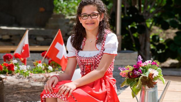 Carina Walker sitzt auf Steiintreppe im Garten. Sie trägt ein rotes Dirndl. Im Hintergrund Schweizer Fähnchen.