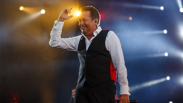 Roland Kaiser mit ausgebreiteten Armen auf der Konzertbühne.