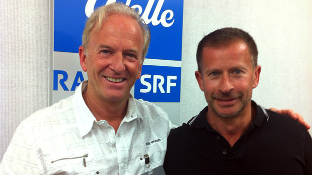 Roland Eberhart und Leonard posieren fürs Foto vor dem blau-weissen Logo der SRF Musikwelle.