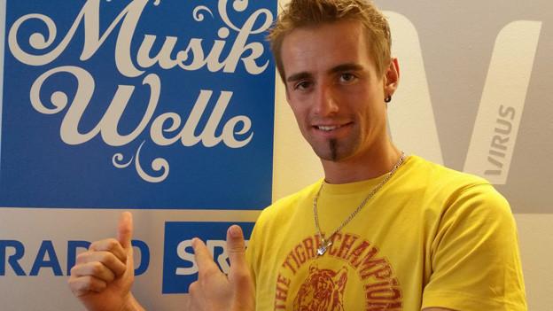 Mit gelben T-Shirt vor Musikwelle Plakat. Florian macht «Daumen hoch».