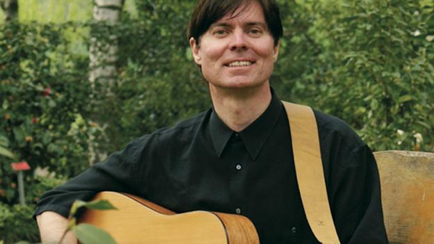 Joe Im Winkelried in Garten sitzend mit Gitarre in der Hand.