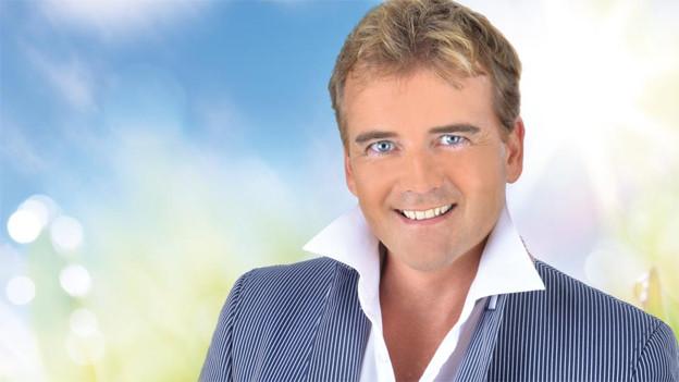 Der Sänger hat strahlend blaue Augen und trägt ein weisses Hemd sowie eine gestreifte Weste.