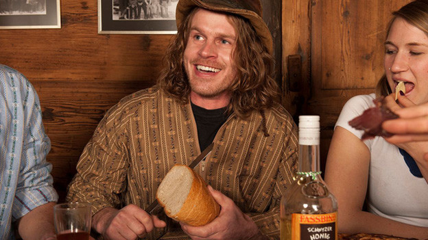 Franz Arnold in ländlichem Wohnzimmer mit Holztäferung. Er sitzt mit seiner Gruppe am Holztisch und schneidet ein Stück Brot ab.
