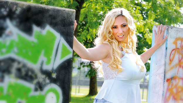 Leona steht zwischen wei Betonmauern, die mit Graffiti vollgeschmiert sind.