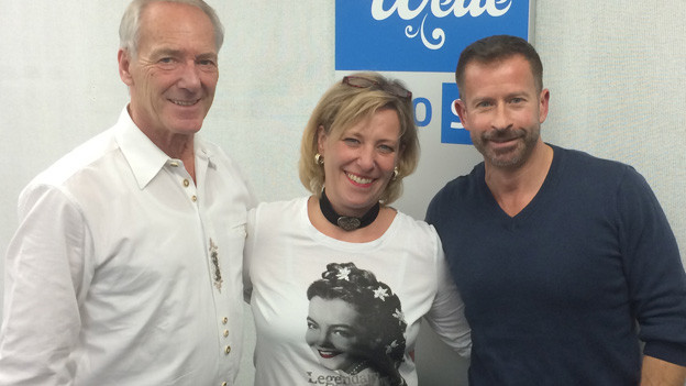 Isabelle und Hans Jauk zu Gast bei Leonard im Studio vor Logo SRF Musikwelle.