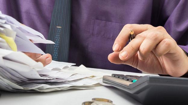 Mann arbeitet einen Stapel Rechnungen ab mit Taschenrechner in der Hand.