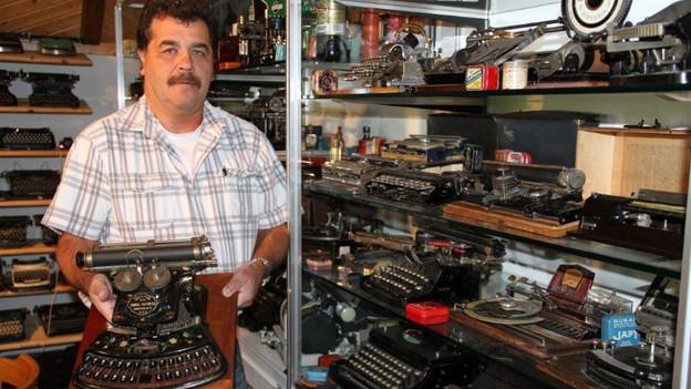 Alex Arca inmitten antiker Schreibmaschinen.