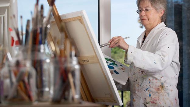 Ältere Frau malt mit PInsel auf Leinwand. Sie trägt einen weissen Arbeitskittel mit Farbtupfern