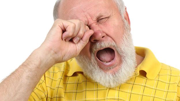 Gähnender, älterer Mann mit Bart.
