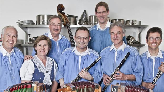 Sechs Musikanten und eine Musikantin mit ihren Instrumenten.
