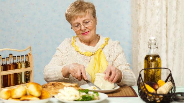 Eine ältere Frau am gedeckten Tisch.