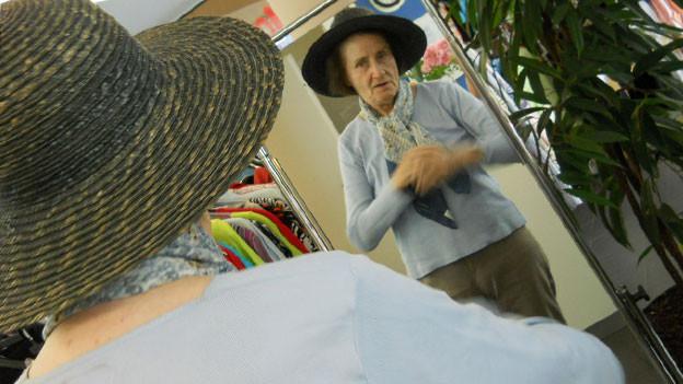 Seniorin betrachtet sich im Spiegel in der Garderobe.