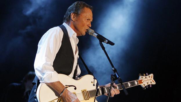 Peter Kraus mit weisser Gitarre singend vor dem Mikrofon.