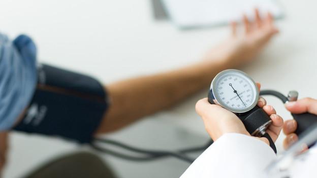 Patientin lässt sich beim Arzt den Blutdruck messen.