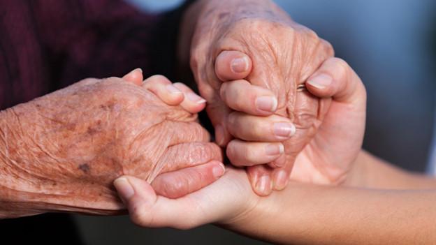Junge Hände greifen alte Hände.