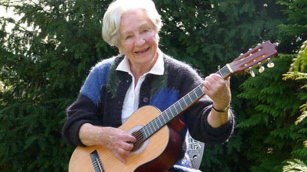 Grauhaarige Dame mit Gitarre in der Hand sitzt im Garten.