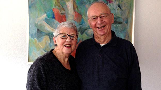 Älteres Ehepaar steht vor Ölgemälde in ihrer Wohnung.