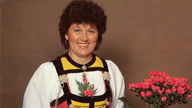 Sonja Aebi in einer Tracht neben einem Strauss Alpenrosen.