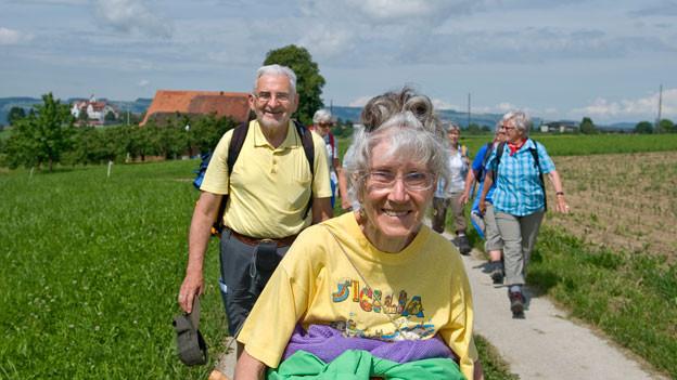 Seniorinnen und Senioren auf kleinem Spazierweg durch hügelige Landschaft.