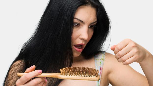 Eine junge Frau blickt entsetzt auf ihre Haarbürste.
