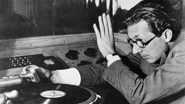 Arthur Welti hebt den Tonarm eines Plattenspielers auf eine Schallplatte.