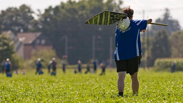 Ein Hornusser mit einer Holzschindel auf der Schulter auf freiem Feld.
