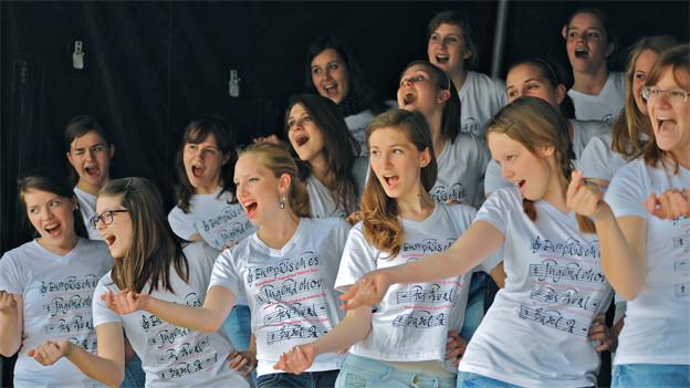 Die Chorsängerinnen tragen T-Shirts mit dem Logo des Europäischen Jugendchor Festivals Basel und singen mit viel Begeisterung.