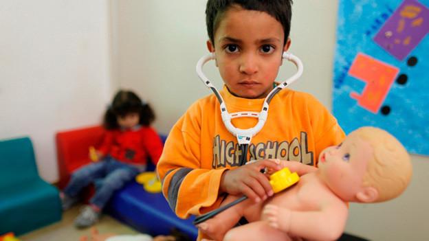 Afrikanischer Junge im Krankenhaus untersucht Puppe mit Stethoskop.